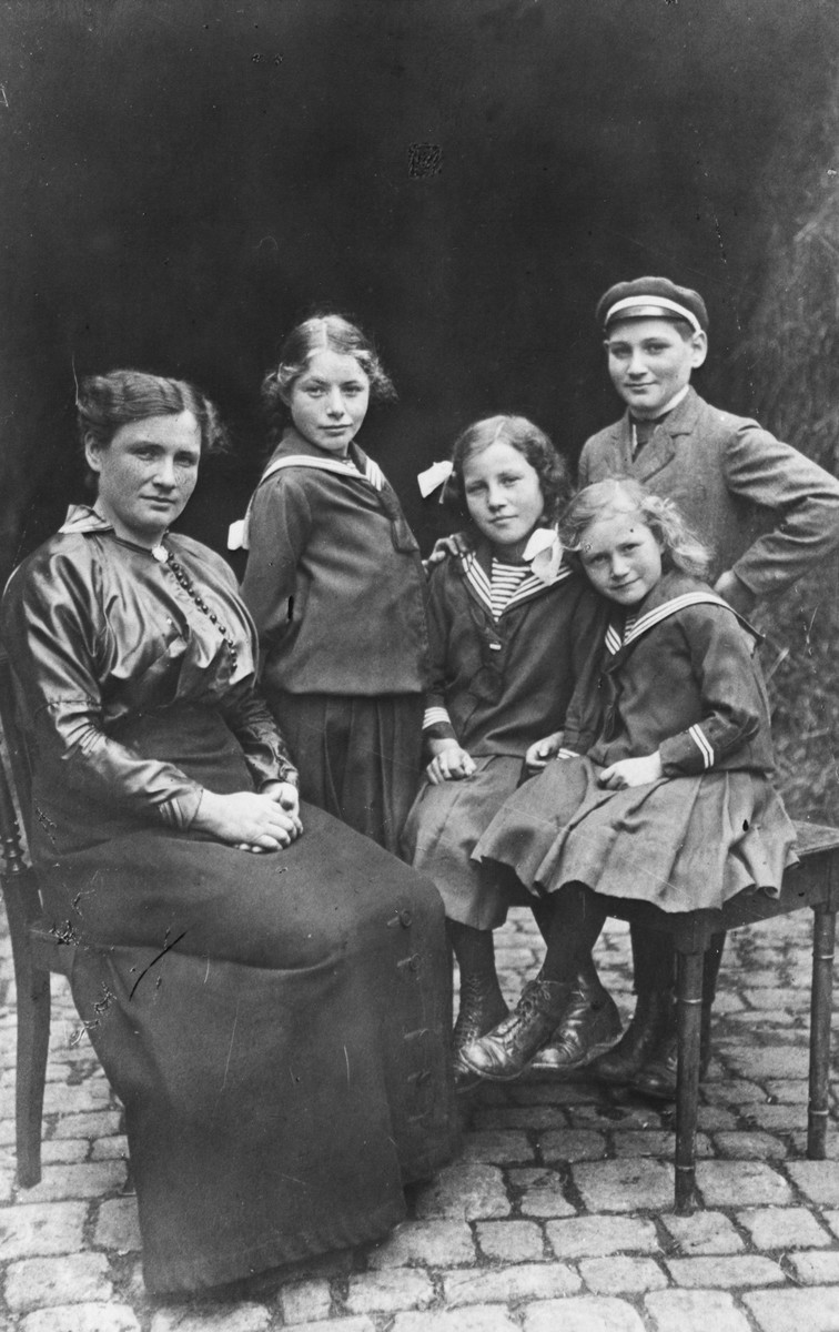 Studio portrait of a German-Jewish family.  Among those pictured are Rosalie Trum together with her children Else, Erna, Alice and Ernst. This is the biological family of Erna Gottschalk, later she was adopted by Gustav and Henriette Gerson.