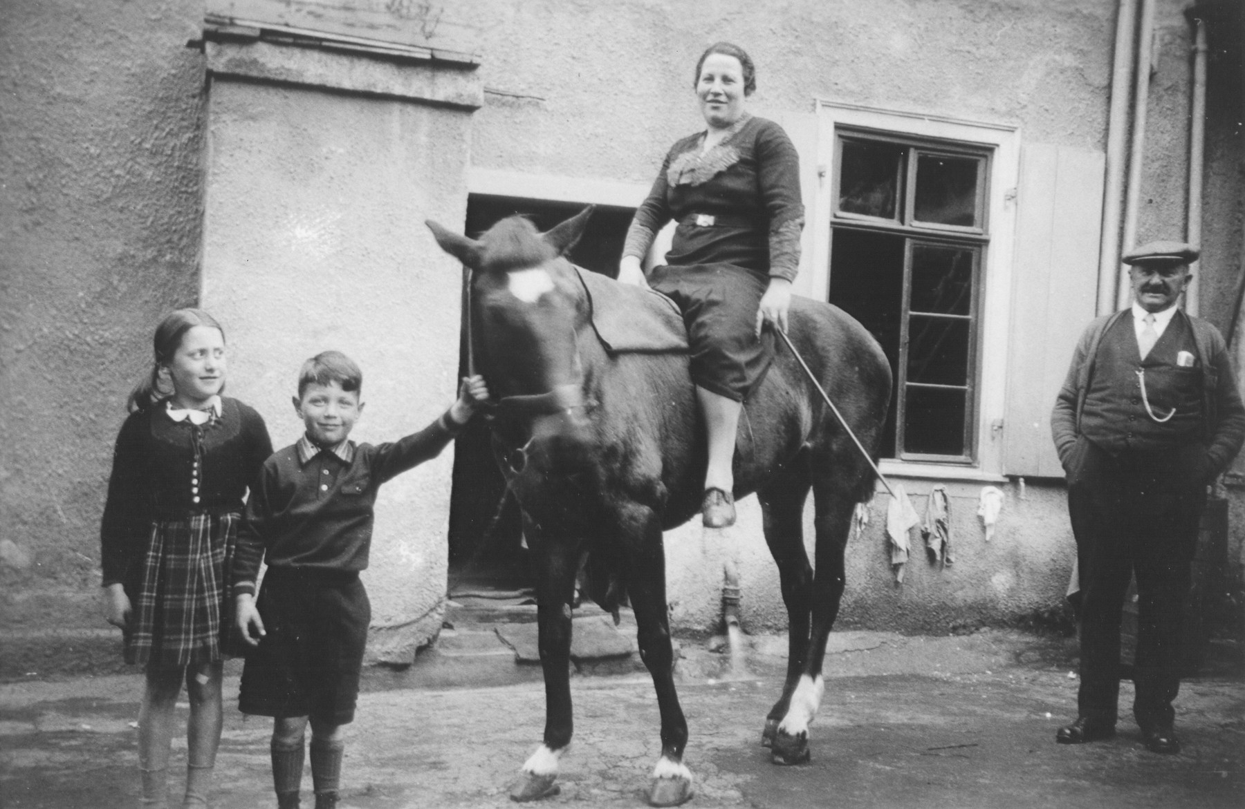 Erna Gottschalk poses on a horse.  Among those pictured are Gustav Gerson (right of Erna) and Alfred Gottschalk (left of Erna).