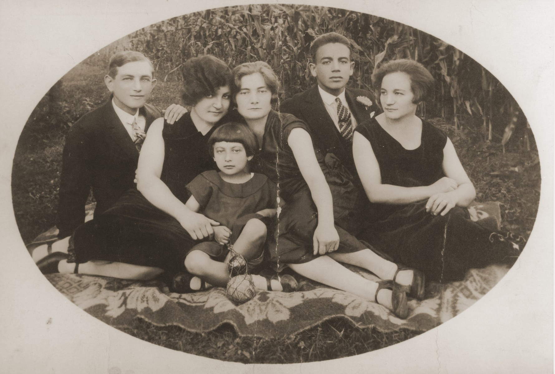 Members of the Gurfein and Saurhaft families pose outside in the grass in Dubiecko, Poland.  Pictured from left to right are: Binyamin Saurhaft, Cila (Gurfein) Saurhaft, Bronia Saurhaft, Ita Gurfein, [first name unknown] Saurhaft, and Devora Saurhaft.