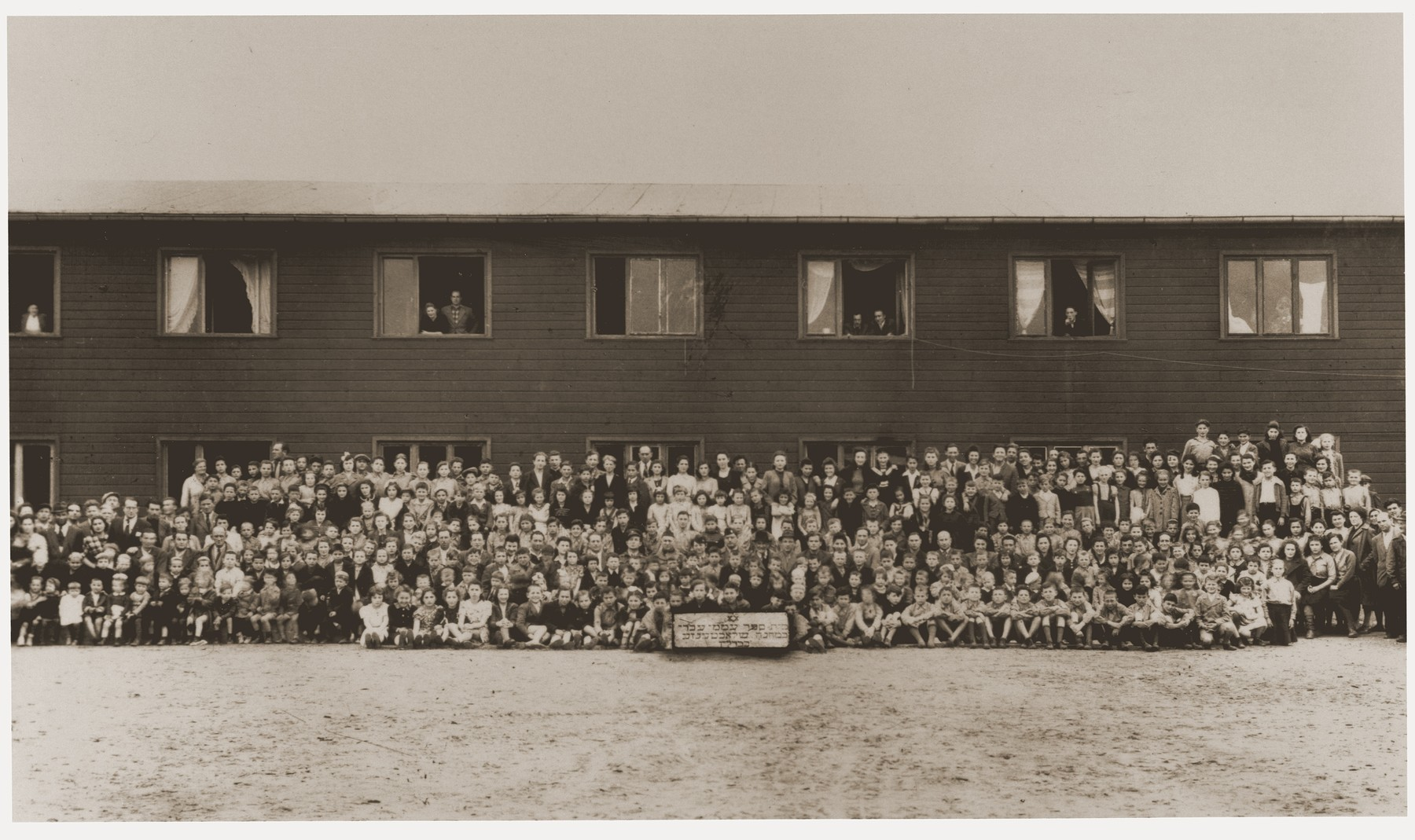 Group portrait of the Hebrew elementary school at the Berlin-Schlachtensee displaced persons camp.  Pictured in the center (four rows above the sign) is Rabbi Herbert Friedman.  Also pictured is Regina Laks.