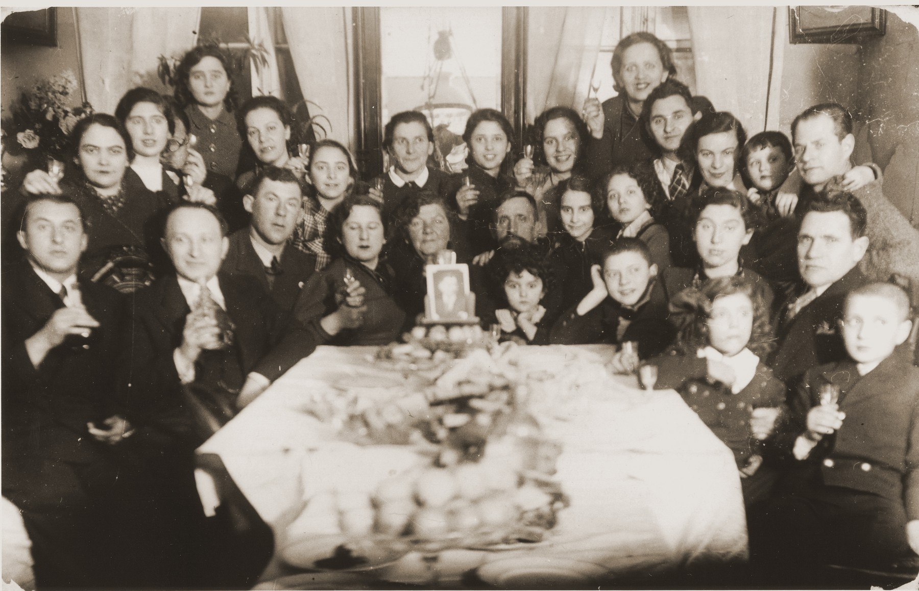 Family gathering to celebrate the marriage of Bezalel Mintz.  He had moved to Belgium and his photo appears on the center of the table.  Of those pictured only two survived.  From left to right those pictured include Benny Fil, Pola Fil, Ida Fil, Chayale Mintz, Rachel Danishevska, Devorah Danishevska, Syma Mintz Crane, Basel Danishevski, Sorele Mintz, Sashe Lepovski, Zirele Lepovski and Nemale Lepovski.