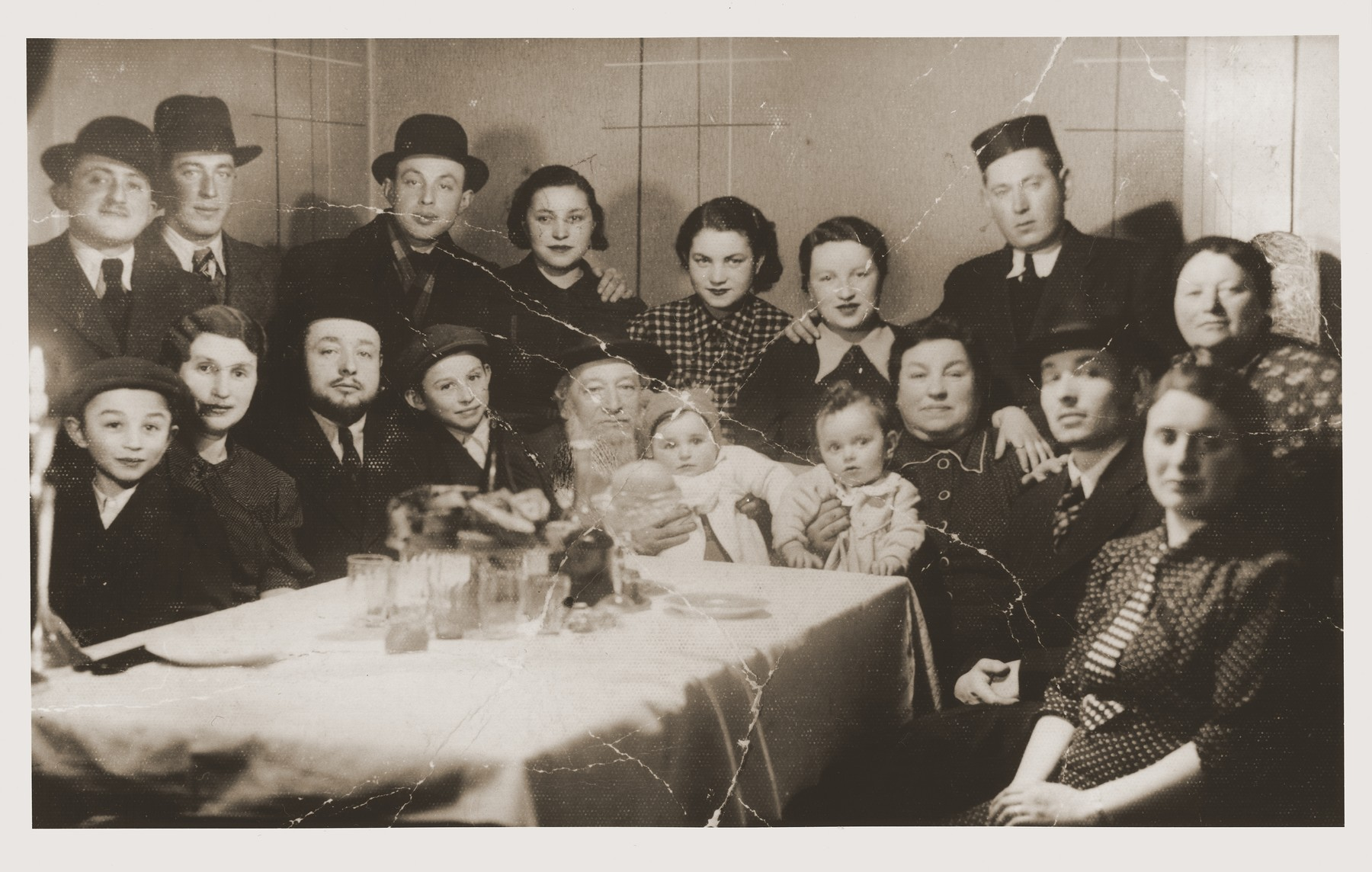 Members of the extended Goldschild family celebrate the holiday of Purim.    128 members of the Goldschild family lived in Khust, most of whom would come together to celebrate Purim.  Seated from left to right are: Yehuda, Berta, Meir, David, Grandfather Herman Goldschild, Esther, Judith, his grandmother Rozsi, Moses and Chana Goldschild.  Standing from left to right are: Chana Goldschild's brother, Hartenbaum, Zsiga Bodner, Vera Fox Goldschild, Rivke Goldschild Hartenbaum, Gittl Klein, Lipe Klein and Chaya Sara.