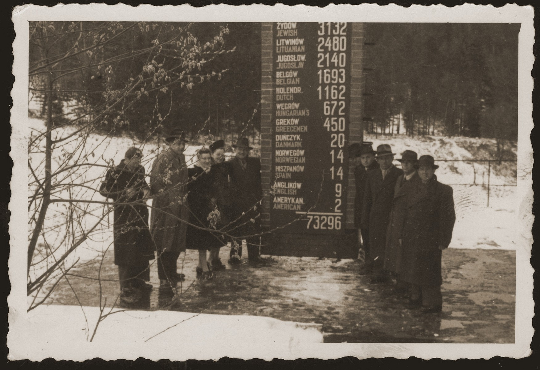 Jewish DPs living in the town of Weiden, Germany, make a pilgrimage to the Flossenbuerg concentration camp on the first or second anniversary of the liberation.    They pose on the roof of the crematorium, next to a memorial listing the number of those who perished in the camp according to nationality.  Among those pictured are Helen Chilewicz and Sala Weingarten and her father.