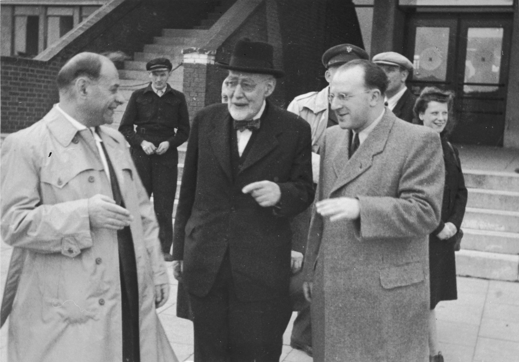 Norbert Wollheim (right) and Rabbi Leo Baeck (center) converse with an official soon after Baeck's arrival in Hamburg at the start of a three week visit to Germany.  Baeck was greeted at the airport by Norbert Wollheim, Chairman of the Central Committee of Jews in the British Zone.  Baeck's trip included participation in an evangelical congress in Darmstadt on October 12, as well as numerous appearances before local Jewish communities.