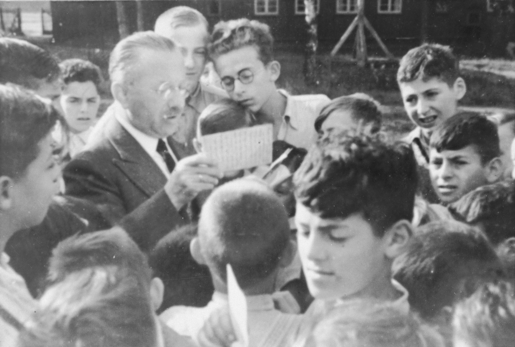Jewish children from Germany at a Kinderlager [children's recreational summer camp] in Horserod, Denmark, gather around an elderly man who is distributing mail.   Among those pictured is Israel Loewenstien, in front, facing the camera while reading a letter.  In 1935-36 Norbert Wollheim was involved in organizing groups of German Jewish youth to attend a summer camp in Denmark.