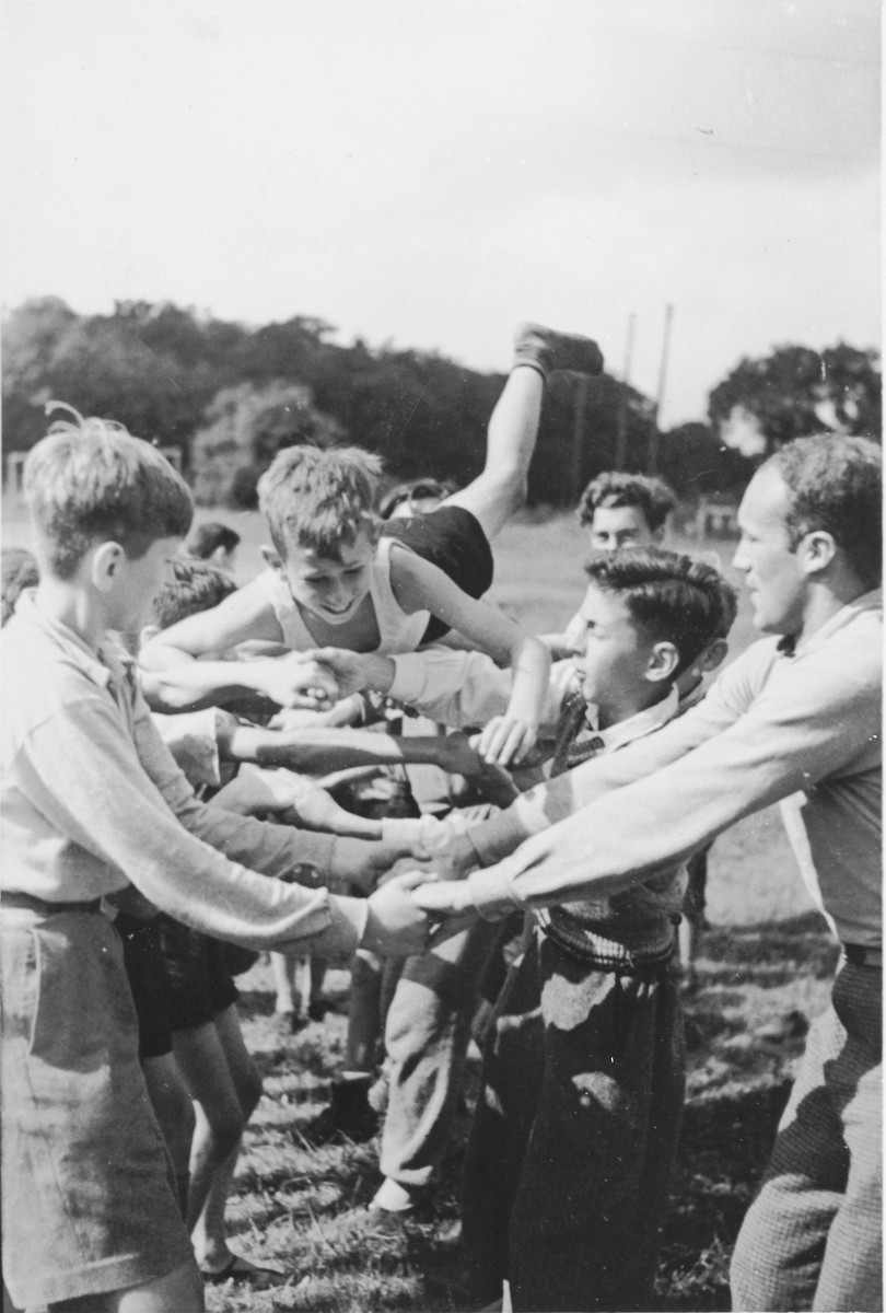 A Jewish child from Germany is passed along a line of children with clasped hands in a game at a Kinderlager [children's recreational summer camp] in Horserod, Denmark.    In 1935-36 Norbert Wollheim was involved in organizing groups of German Jewish youth to attend a summer camp in Denmark.