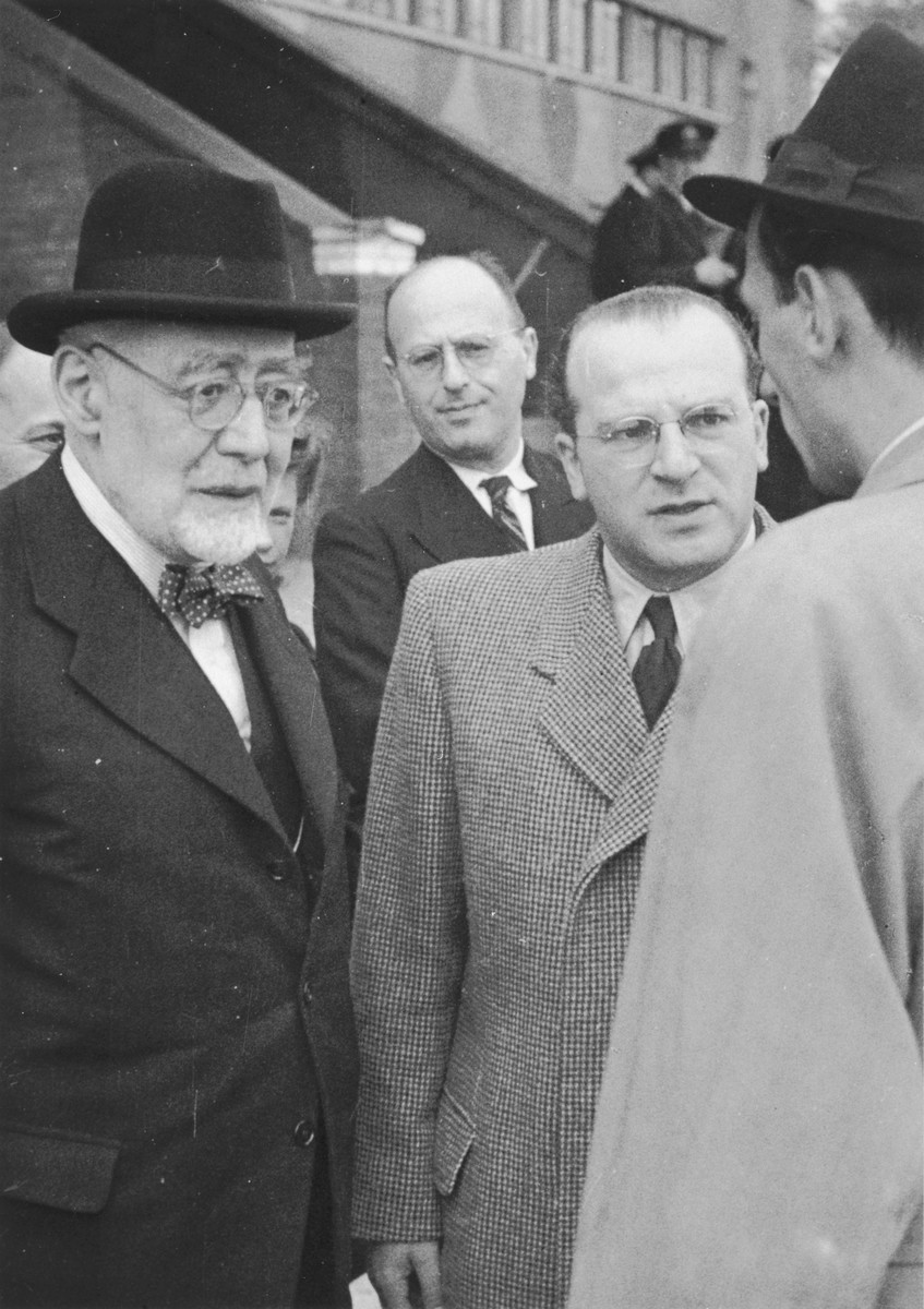 Rabbi Leo Baeck and Norbert Wollheim converse with an official soon after Baeck's arrival in Hamburg at the start of a three week visit to Germany.  Baeck was greeted at the airport by Norbert Wollheim, Chairman of the Central Committee of Jews in the British Zone.  Baeck's trip included participation in an evangelical congress in Darmstadt on October 12, as well as numerous appearances before local Jewish communities.