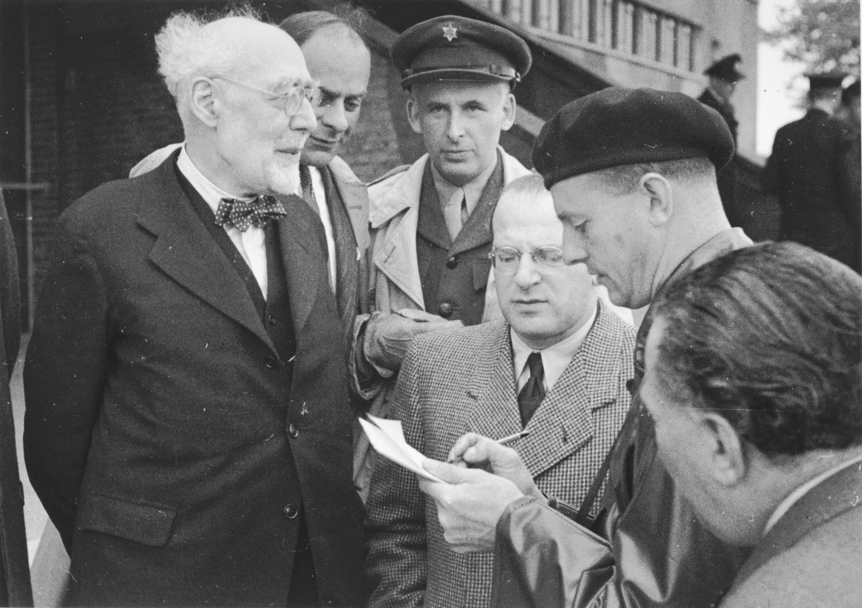Rabbi Leo Baeck is interviewed by a British soldier upon his arrival in Hamburg at the start of a three week visit to Germany.     Also pictured are Norbert Wollheim (wearing glasses in the center) and Heinz Salomon, Leader of Jewish Welfare after the war (behind Leo Baeck).  Baeck was greeted at the airport by Norbert Wollheim, Chairman of the Central Committee of Jews in the British Zone.  Baeck's trip included participation in an evangelical congress in Darmstadt on October 12, as well as numerous appearances before local Jewish communities.