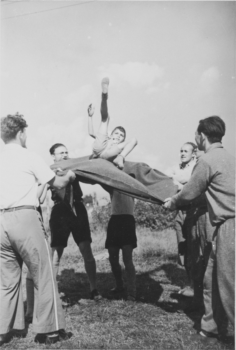 A Jewish child from Germany is tossed into the air on a blanket at a Kinderlager [children's recreational summer camp] in Horserod, Denmark.    In 1935-36 Norbert Wollheim was involved in organizing groups of German Jewish youth to attend a summer camp in Denmark.
