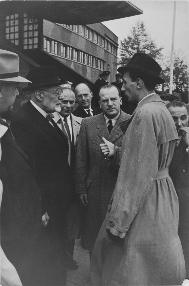 Norbert Wollheim (center, right) and Rabbi Leo Baeck (left) converse with an official soon after Baeck's arrival in Hamburg at the start of a three week visit to Germany.  Baeck was greeted at the airport by Norbert Wollheim, Chairman of the Central Committee of Jews in the British Zone.  Baeck's trip included participation in an evangelical congress in Darmstadt on October 12, as well as numerous appearances before local Jewish communities.during his visit to Germany.