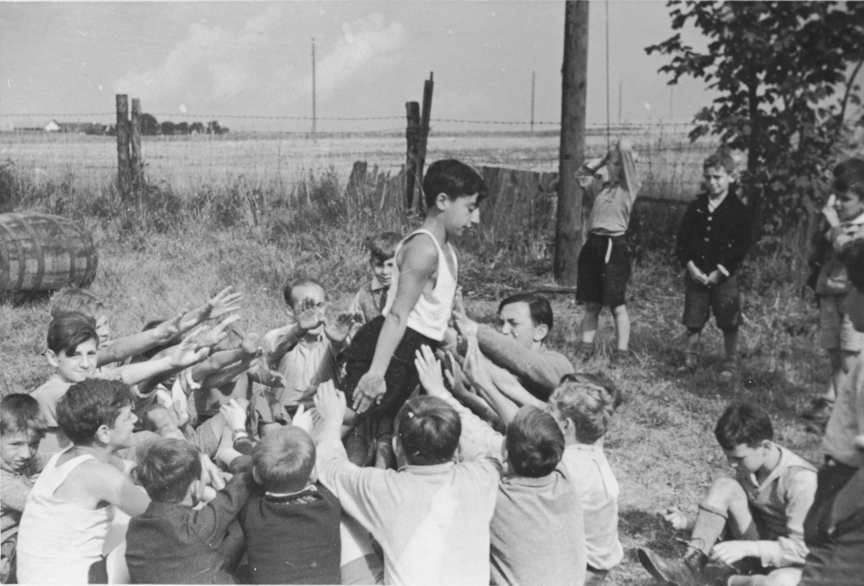 A Jewish child from Germany is passed around a circle in a trust game at a Kinderlager [children's recreational summer camp] in Horserod, Denmark.    In 1935-36 Norbert Wollheim was involved in organizing groups of German Jewish youth to attend a summer camp in Denmark.