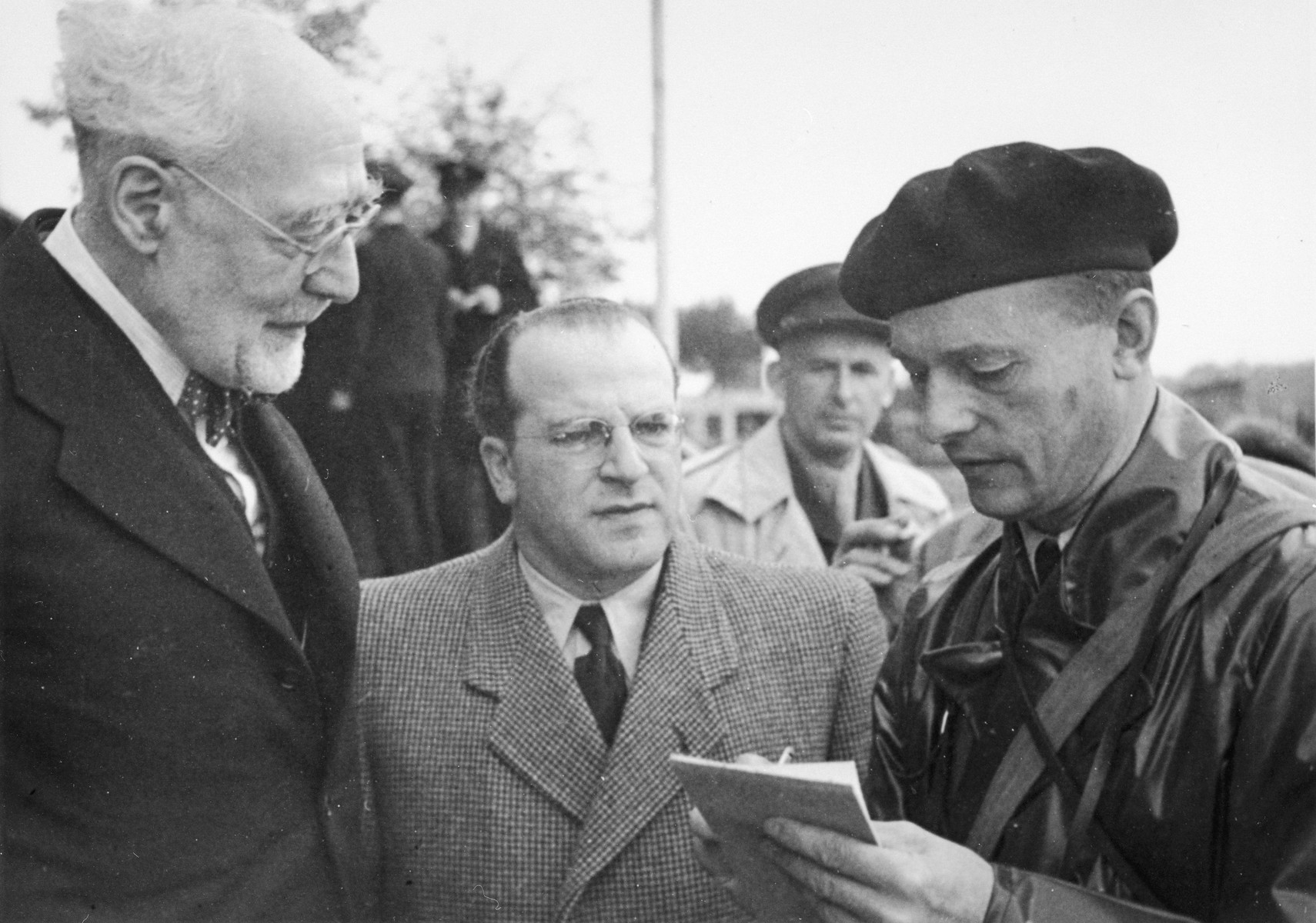 Rabbi Leo Baeck is interviewed by a British soldier upon his arrival in Hamburg at the start of a three week visit to Germany.  Also pictured in Norbert Wollheim (wearing glasses in the center).  Baeck was greeted at the airport by Norbert Wollheim, Chairman of the Central Committee of Jews in the British Zone.  Baeck's trip included participation in an evangelical congress in Darmstadt on October 12, as well as numerous appearances before local Jewish communities.