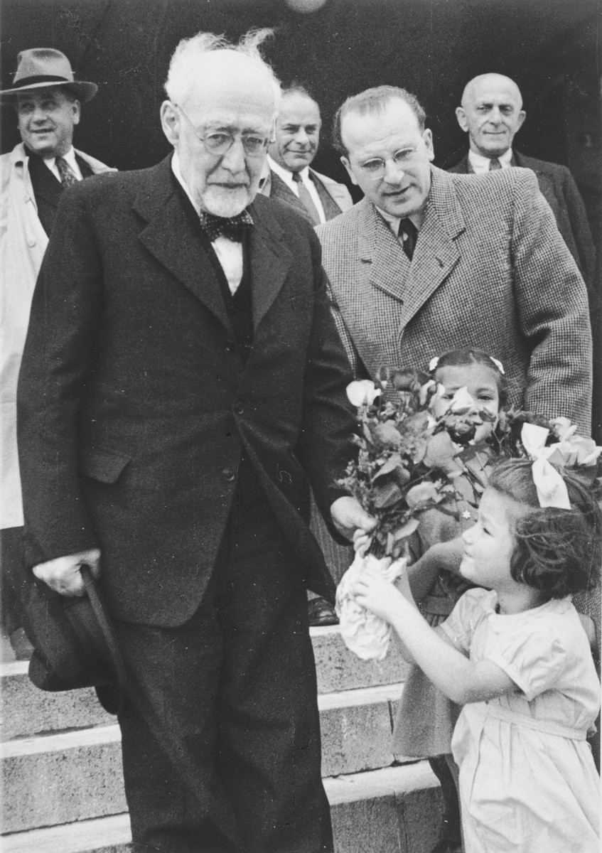 Reha Fabian presents a bouquet of flowers to Rabbi Leo Baeck upon his arrival in Hamburg at the start of a three week visit to Germany.  Reha's sister, Judis, is standing in front of Norbert Wollheim and her father, Hans Erich Fabian, can be seen in the background.  Baeck was greeted at the airport by Norbert Wollheim, Chairman of the Central Committee of Jews in the British Zone.  Baeck's trip included participation in an evangelical congress in Darmstadt on October 12, as well as numerous appearances before local Jewish communities.