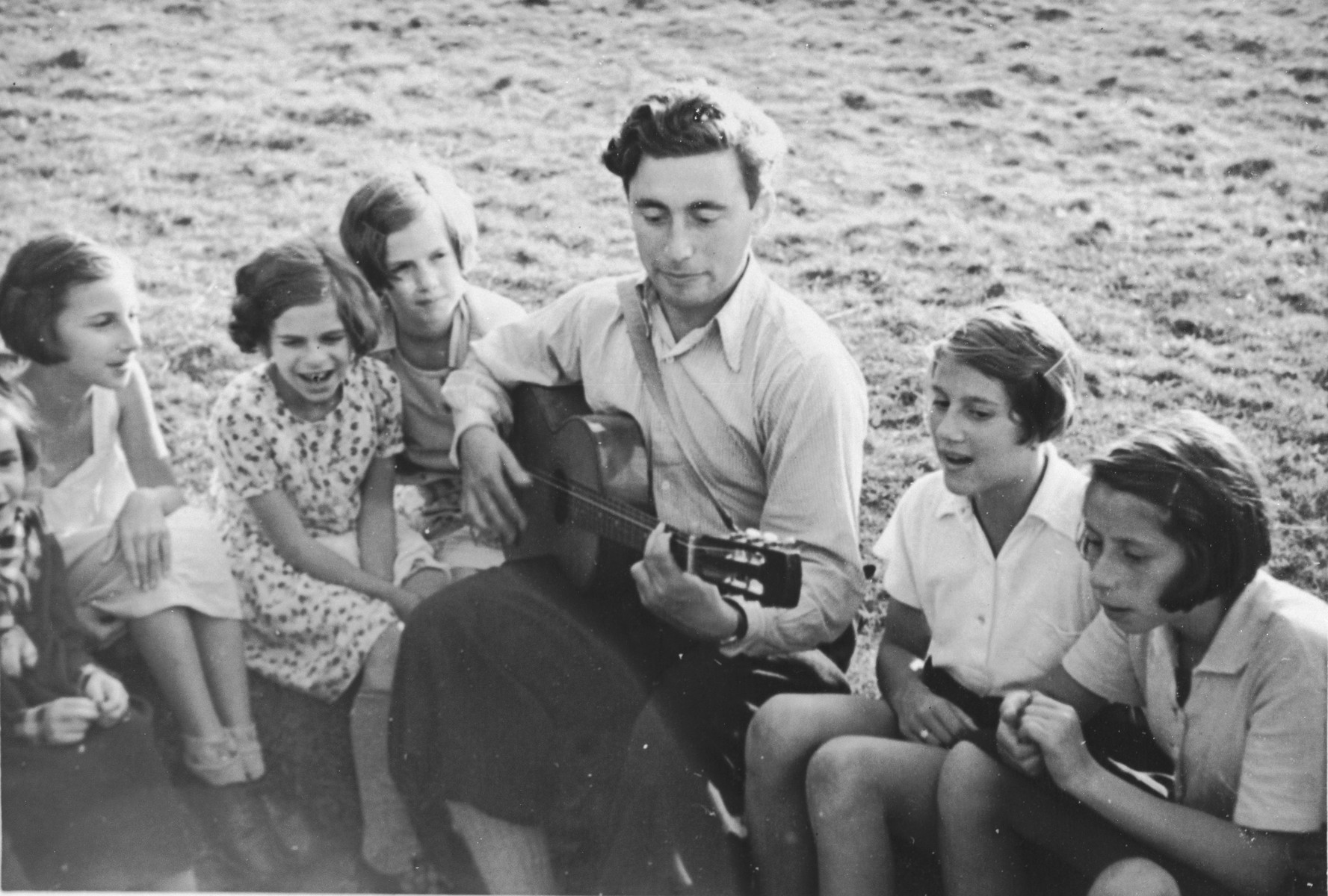 A group of Jewish girls from Germany sings along as one of their counselors play the guitar at a Kinderlager [children's recreational summer camp] in Horserod, Denmark.    In 1935-36 Norbert Wollheim was involved in organizing groups of German Jewish youth to attend a summer camp in Denmark.
