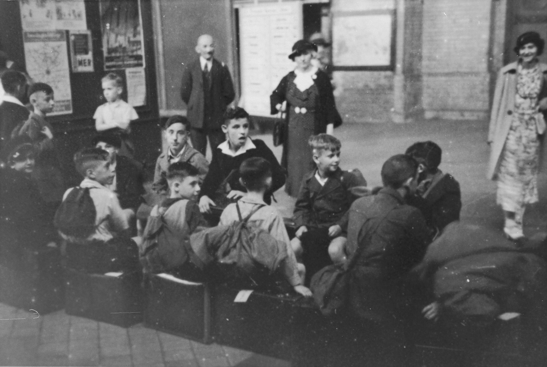 Jewish children from Germany who are on their way to a Kinderlager [children's recreational summer camp] in Horserod, Denmark, wait to board a train in the waiting room of the train station.   In 1935-36 Norbert Wollheim was involved in organizing groups of German Jewish youth to attend a summer camp in Denmark.