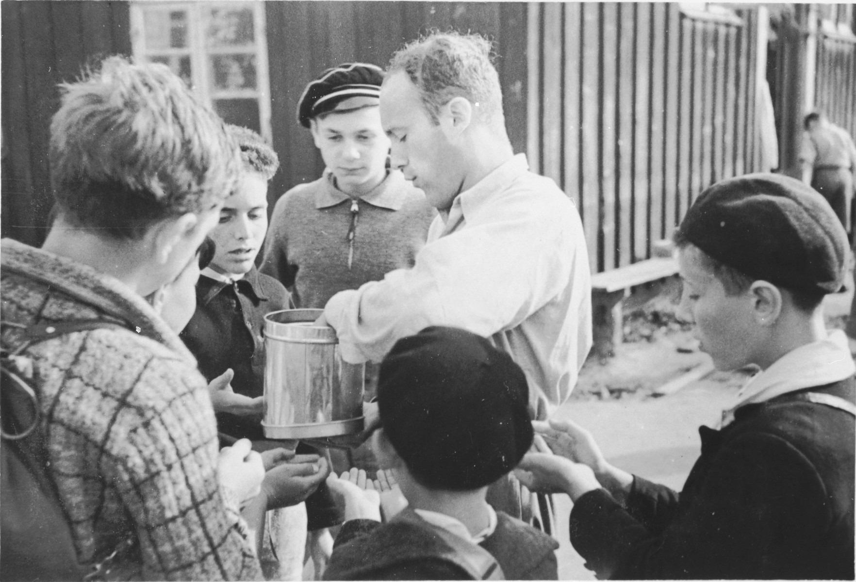 A counselor distributes food or seeds to a group of Jewish boys from Germany at a Kinderlager [children's recreational summer camp] in Horserod, Denmark.    In 1935-36 Norbert Wollheim was involved in organizing groups of German Jewish youth to attend a summer camp in Denmark.