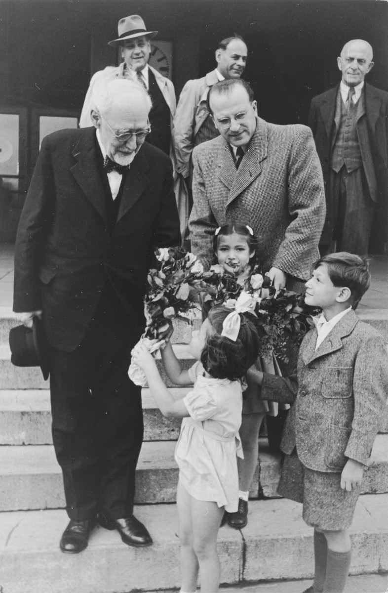Joel, Reha and Judis Fabian present a bouquet of flowers to Rabbi Leo Baeck upon his arrival in Hamburg at the start of a three week visit to Germany.  The three children are survivors of Theresienstadt.  Their father Hans Erich Fabian is standing in the background wearing a hat.  Baeck was greeted at the airport by Norbert Wollheim, Chairman of the Central Committee of Jews in the British Zone.  Baeck's trip included participation in an evangelical congress in Darmstadt on October 12, as well as numerous appearances before local Jewish communities.