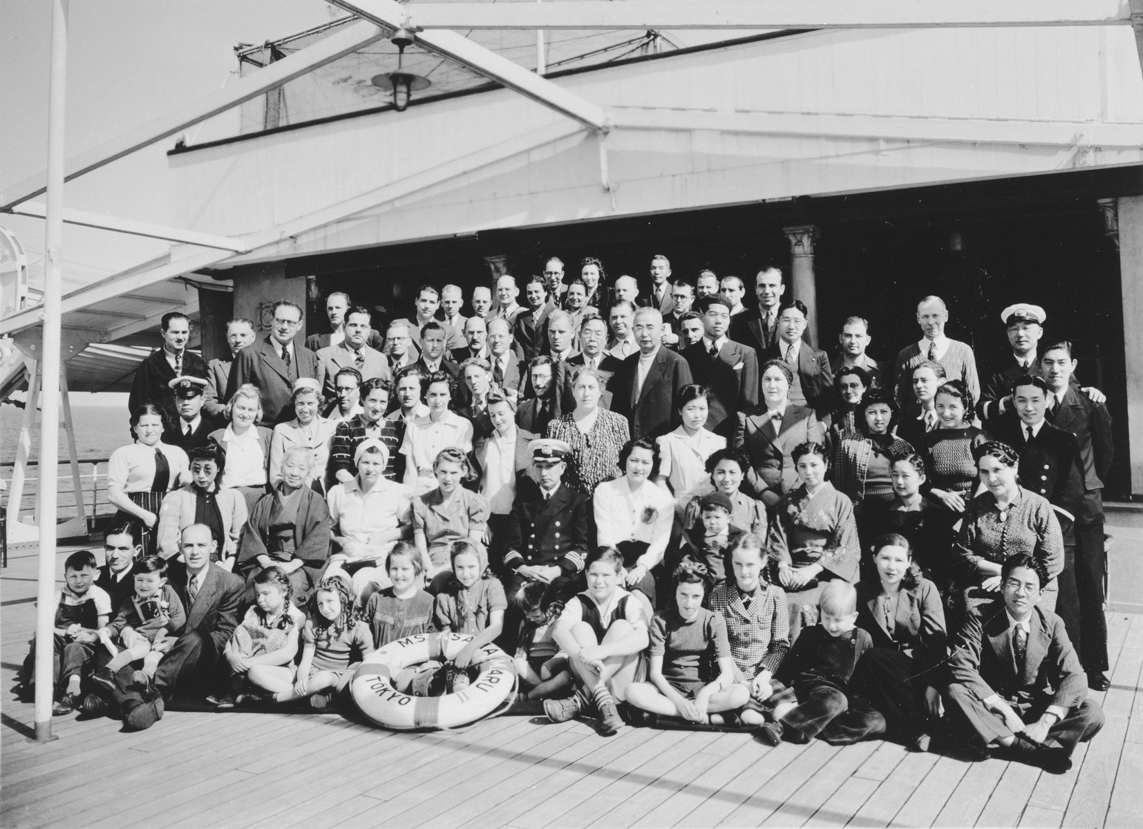 Group portrait of passengers on board the Asama Maru en route from Yokohama via Oahu to San Francisco.  Among those pictured are the ships' crew, Irena Malowist (sitting in the front row, fifth from the right); her mother Maria Malowist (standing in the third row, sixth from the left) and her father Szymon Malowist (standing at the back).