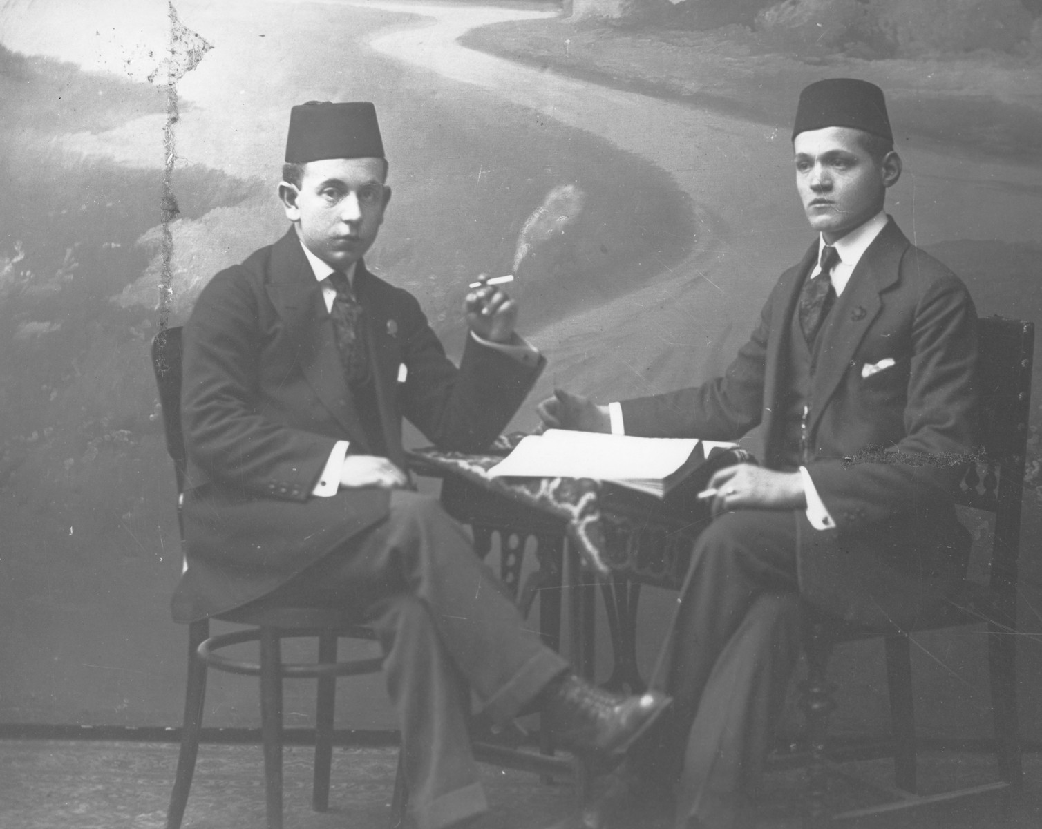 Studio portrait of two male Jewish students smoking cigarettes.  Pictured on the left is Michael Kabilio.