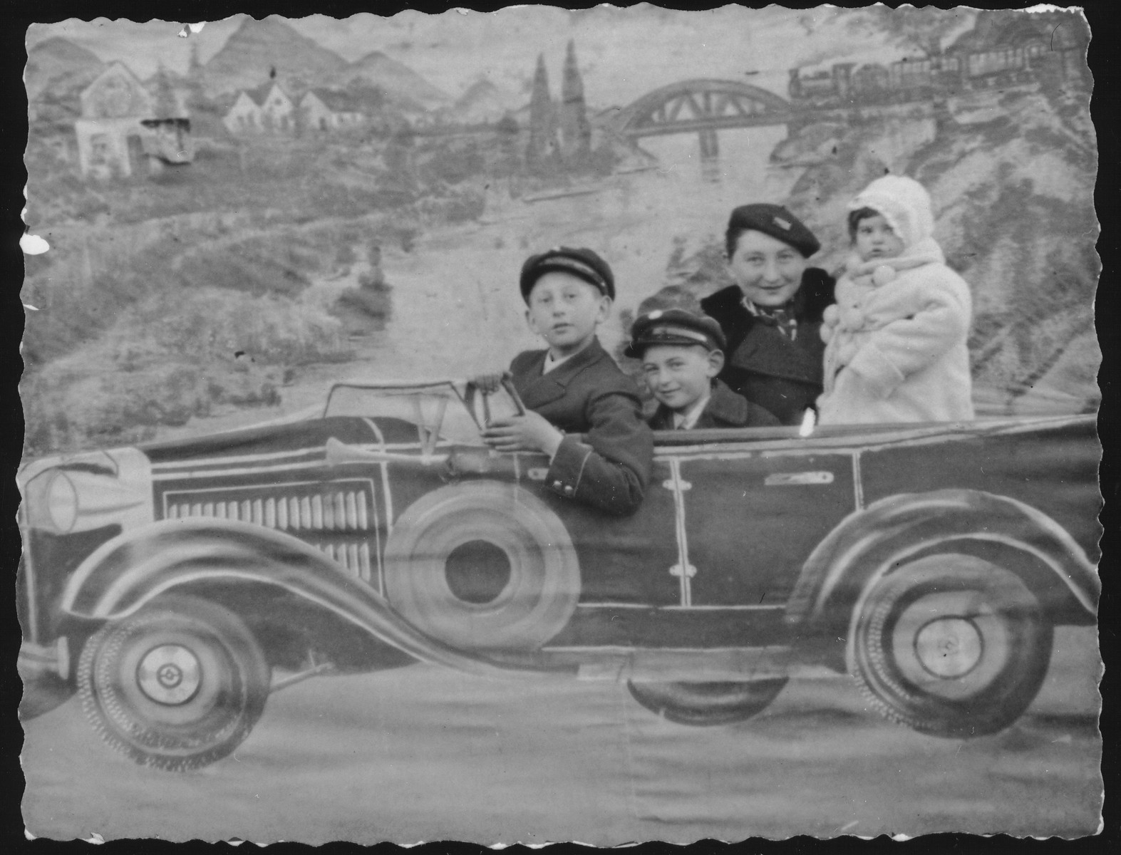 Zipporah (Katz) Sonenson poses with her younger brother and her two children against a backdrop of a sports car in the photo studio owned by her parents, Yitzhak and Alte Katz in Eisiskes.  Pictured from left to right are: Avigdor Katz, Yitzhak Uri Sonenson, Zipporah (Katz) Sonenson and Yaffa Sonenson.  After the paving of the Pilsudski Highway, to own or ride in a car became the aspiration of the younger generation in Eisiskes.  In the 1930s the sports car was the most popular backdrop in the Katz photography studio.  Avigdor Katz was killed by the Germans during the September 1941 mass shooting action in Eisiskes.
