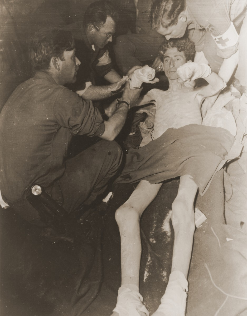 American medics treat an emaciated soldier, Pvt. Alvin L. Abrams of Philadelphia, one of 63 American POWs who survived a death march from the Berga concentration camp and was liberated by soldiers of the 357th Infantry Regiment.