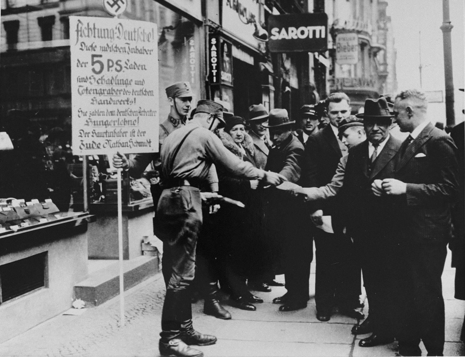"SA pickets distribute boycott pamphlets to German pedestrians.  The sign held by one of them reads: ""Attention Germans. These Jewish owners of [five and dime] stores are the parasites and gravediggers of German craftsmen.  They pay starvation wages to German workers.  The chief owner is the Jew, Nathan Schmidt."""
