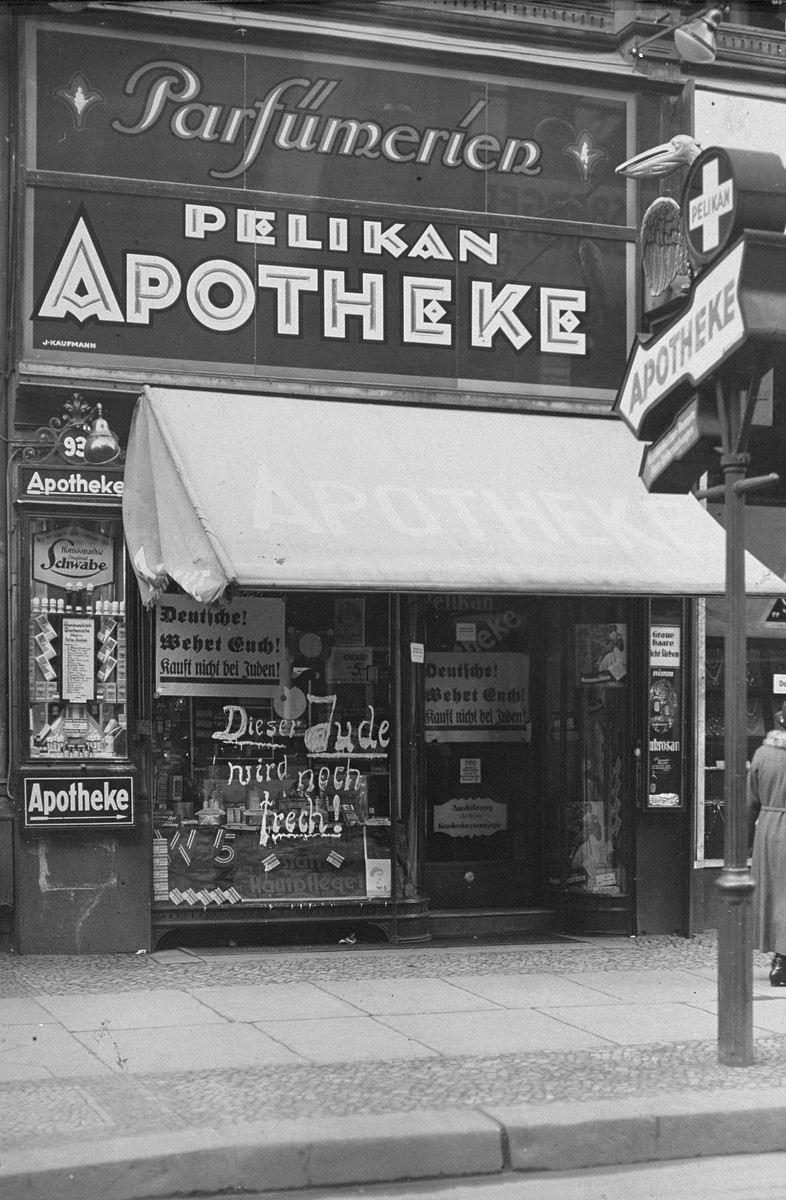 "Boycott signs and anti-Semitic graffiti on the store-front of Pelikan Apotheke, a Jewish-owned pharmacy in Berlin.  The graffiti reads:  ""This Jew is still insolent!"""