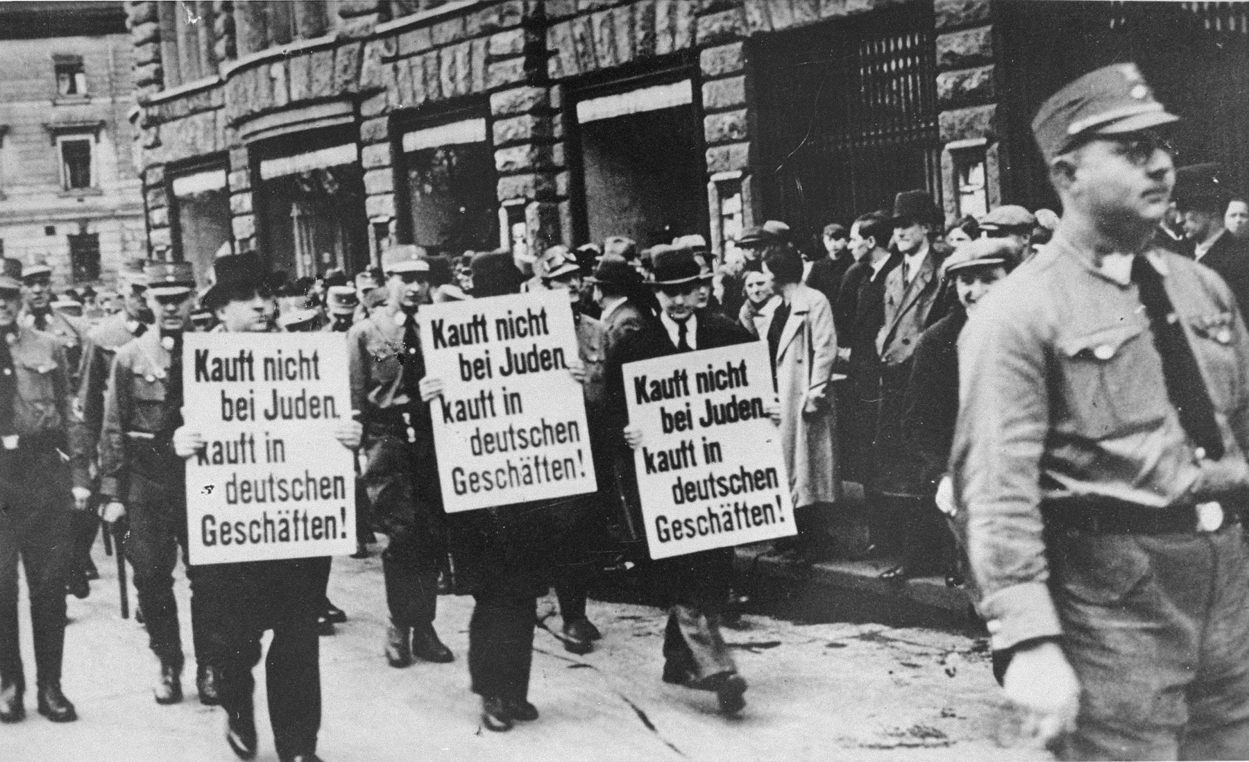 "Three Jewish businessmen are paraded down Bruehl Strasse in central Leipzig, carrying signs that read:  ""Don't buy from Jews;  Shop at German stores!""   The third marcher from the left is Chaim Bleiweiss, the donor's father.  Bleiweiss owned a fur store located at Bruehl Strasse 68.  The photo was produced as a postcard and sold at kiosks in Leipzig, where Chaim Bleiweiss purchased it."