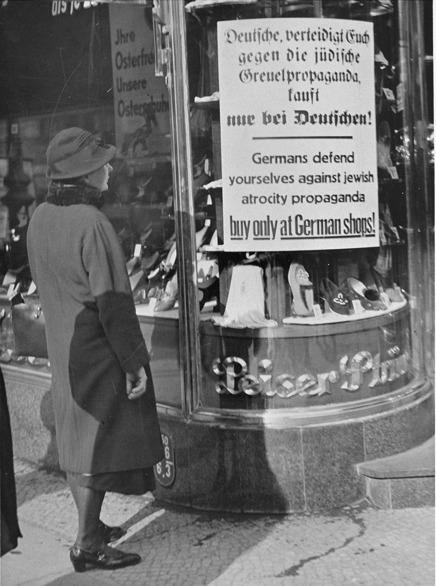 """A woman reads a boycott sign posted in the window of a Jewish-owned department store.    The sign reads: """"Germans defend yourselves against Jewish atrocity propaganda, buy only at German shops!"""""""