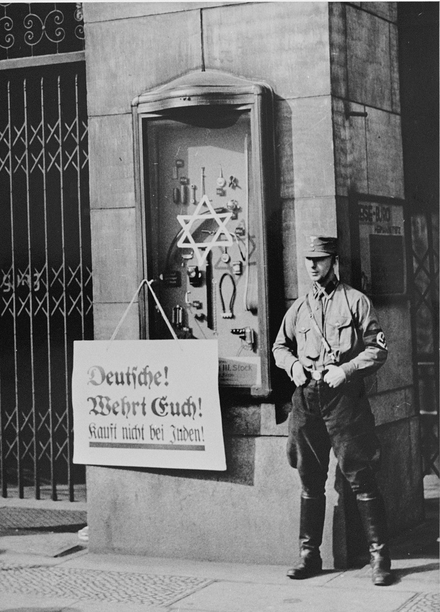 """An SA picket stands in front of the Jewish-owned Tietz department store wearing a boycott sign that reads:  """"Germans defend yourselves; don't buy from Jews!"""""""