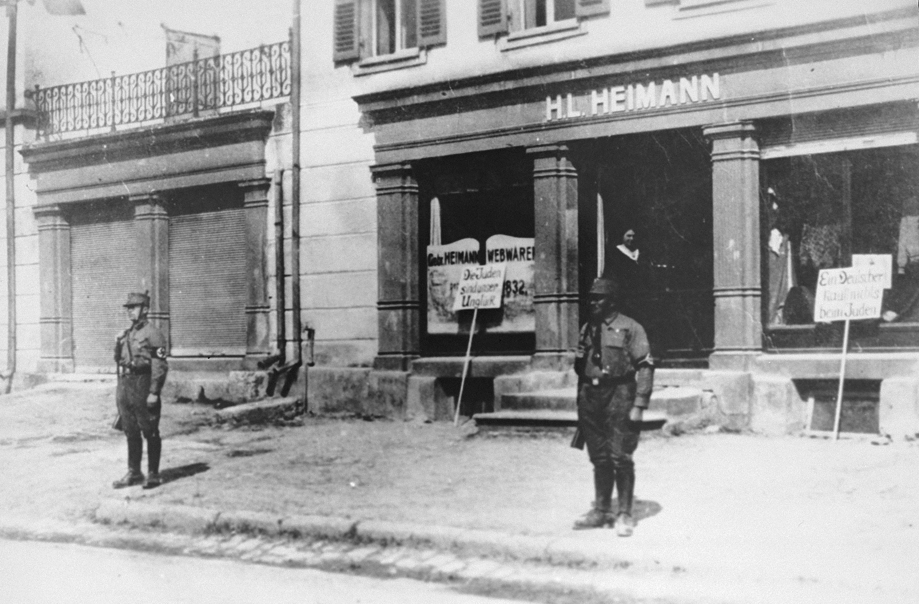 "Two Nazi stormtroopers stand guard in front of the H. L. Heimann store in Bopfingen, to prevent would-be shoppers from violating the Nazi boycott of Jewish-owned businesses.  Two signs have been placed in front of the store.  The sign on the left reads: ""The Jews are our Misfortune.""  The sign on the right reads:  ""A German buys nothing from Jews.""  The business belonged to the donor's father.  Pictured at the entrance to the store is Sali Heimann, who was later killed in a concentration camp in Riga."