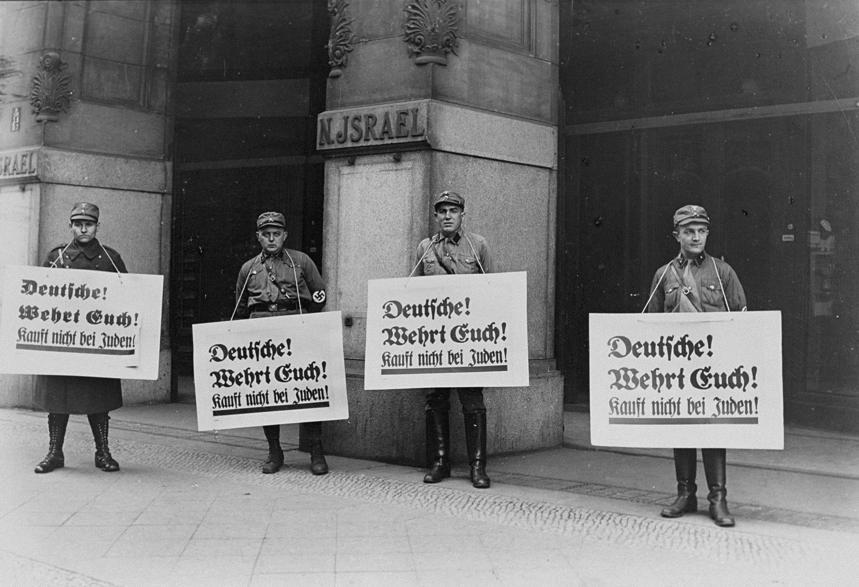 "Four SA pickets wearing boycott signs stand in front of the Jewish-owned N. Israel department store in Berlin.    The signs read:  ""Germans, defend yourselves.  Don't buy from Jews!"""