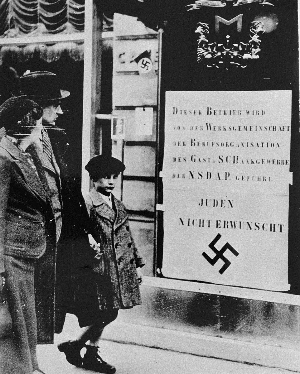 Viennese pedestrians view a large Nazi sign posted on a restaurant window informing the public that this business is run by an organization of the National Socialist Party and that Jews are not welcome.