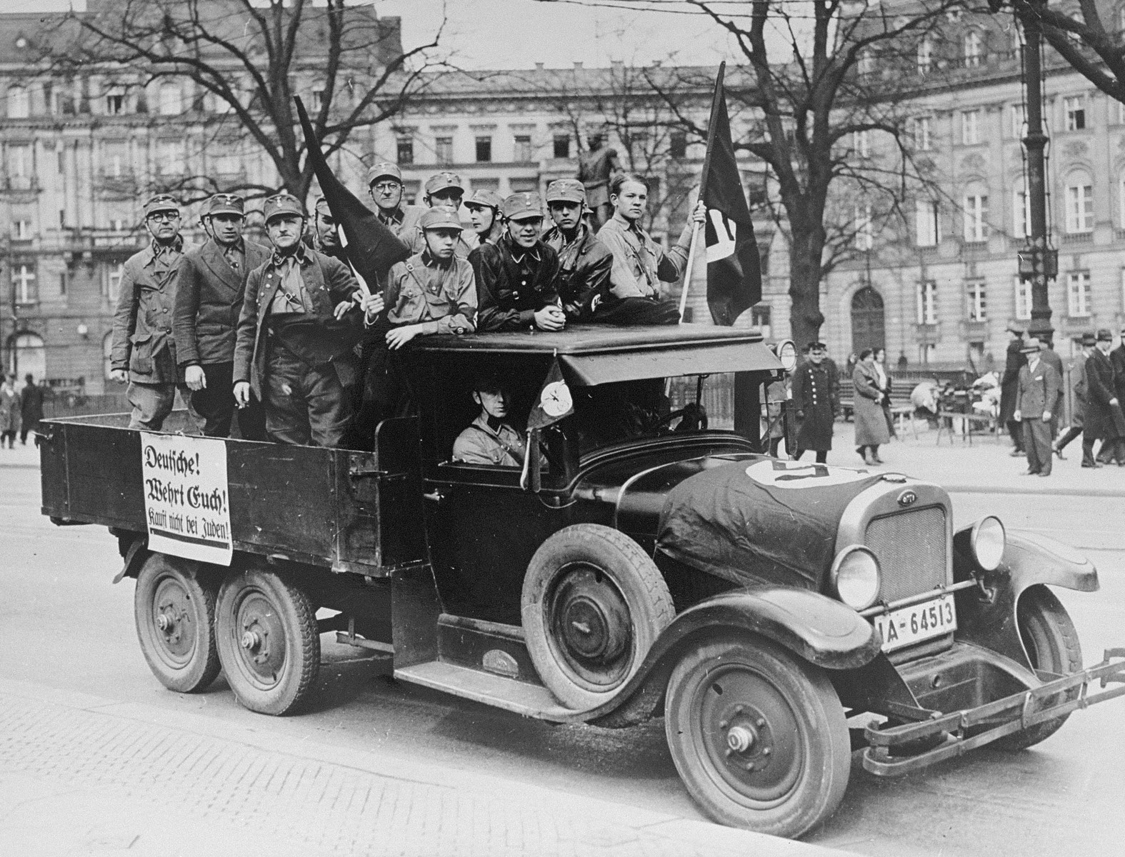 A group of SA members ride through the streets of Berlin in the back of a truck, exhorting Germans to boycott Jewish businesses.