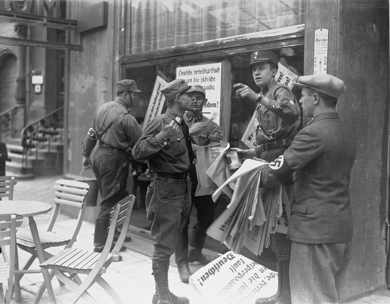 "An SA member instructs others where to post anti-Jewish boycott signs on a commercial street in Germany.    A German civilian wearing a Nazi armband holds a sheaf of anti-Jewish boycott signs, while SA members paste them on a Jewish-owned business.  Most of the signs read, ""Germans defend yourselves against Jewish atrocity propaganda/Buy only at German stores."""