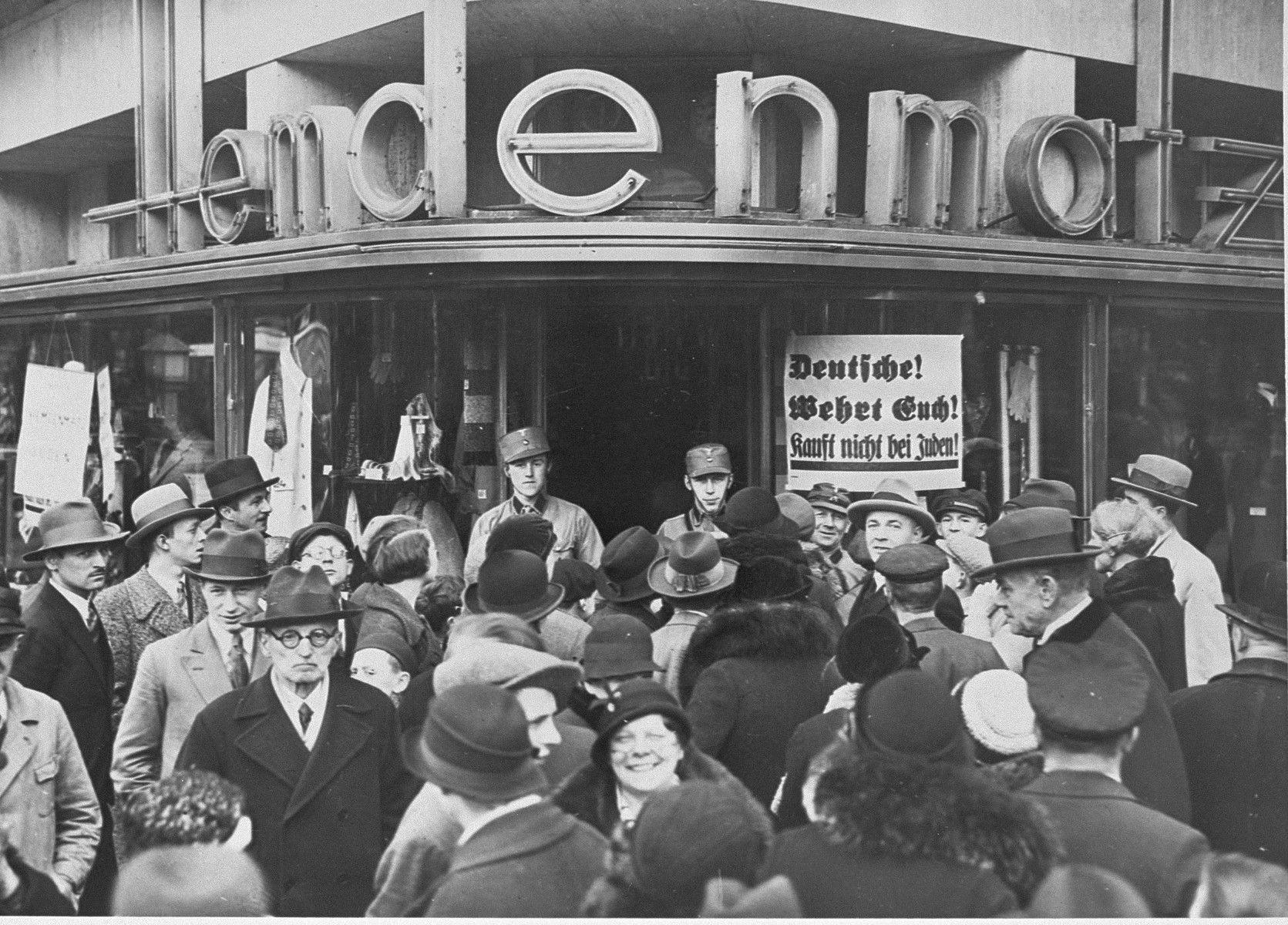 A crowd of Germans is gathered in front of a Jewish-owned department store in Berlin on the first day of the boycott.  Signs exhorting Germans not to buy from Jews are posted on the store front.