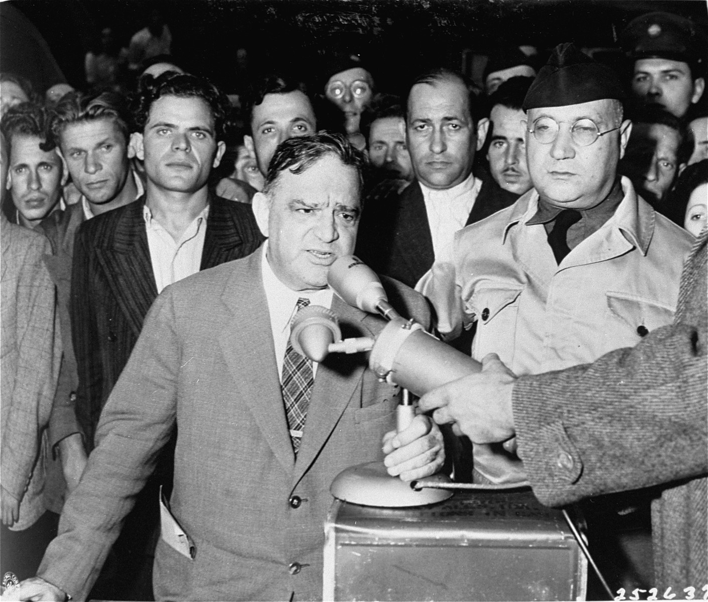 UNRRA Director General Fiorello LaGuardia delivers a speech at the Berlin-Schlachtensee displaced persons camp.    Also pictured is UNRRA Schlachtensee camp director Harold Fishbein (standing next to LaGuardia on the right).