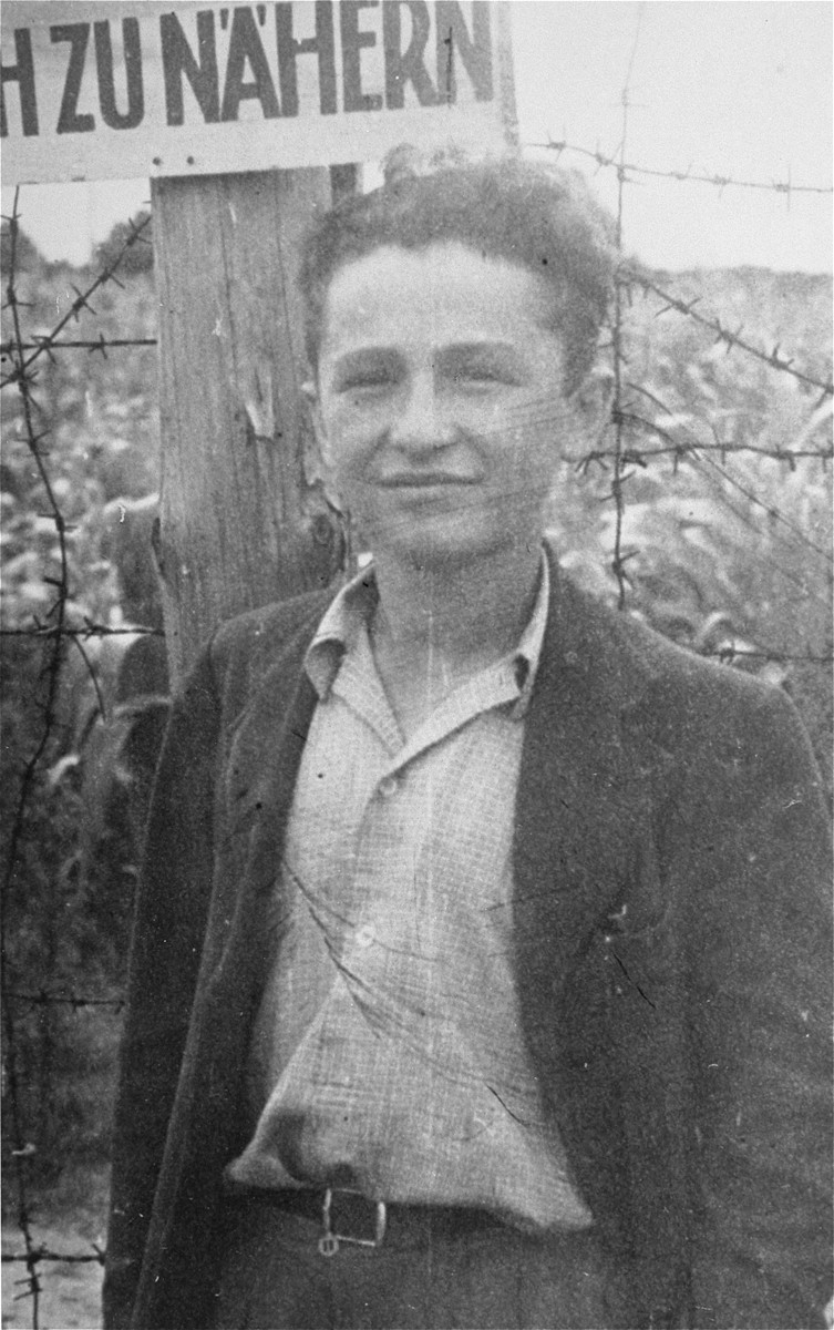 Moniek Gliklich stands in front of a barbed wire fence at Berlin-Schlachtensee DP camp.