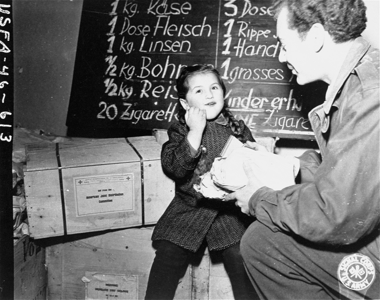 Harry Weinsaft of the American Jewish Joint Distribution Committee, gives food to three-year-old Renati Rulhater, a Jewish DP child in Vienna.  The campaign to distribute food to needy refugees in Vienna is sponsored by the Jewish Joint Welfare Association of Vienna in conjunction with the JDC.