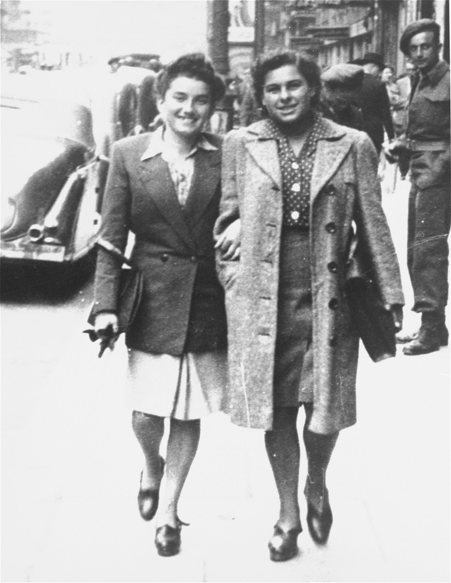 Two Jewish DPs walk along a street in Brussels, Belgium.  Pictured are Hanka Wajcblum (right) and Marta Bindiger Cige (left).   The two women became friends while they were prisoners at Auschwitz-Birkenau.  Marta took care of Hanka after her sister, Ester Wajcblum, was arrested and executed as a co-conspirator in the revolt of October 1944.  Marta was born in Bardejov, Czechoslovakia and was deported to Auschwitz in 1942.