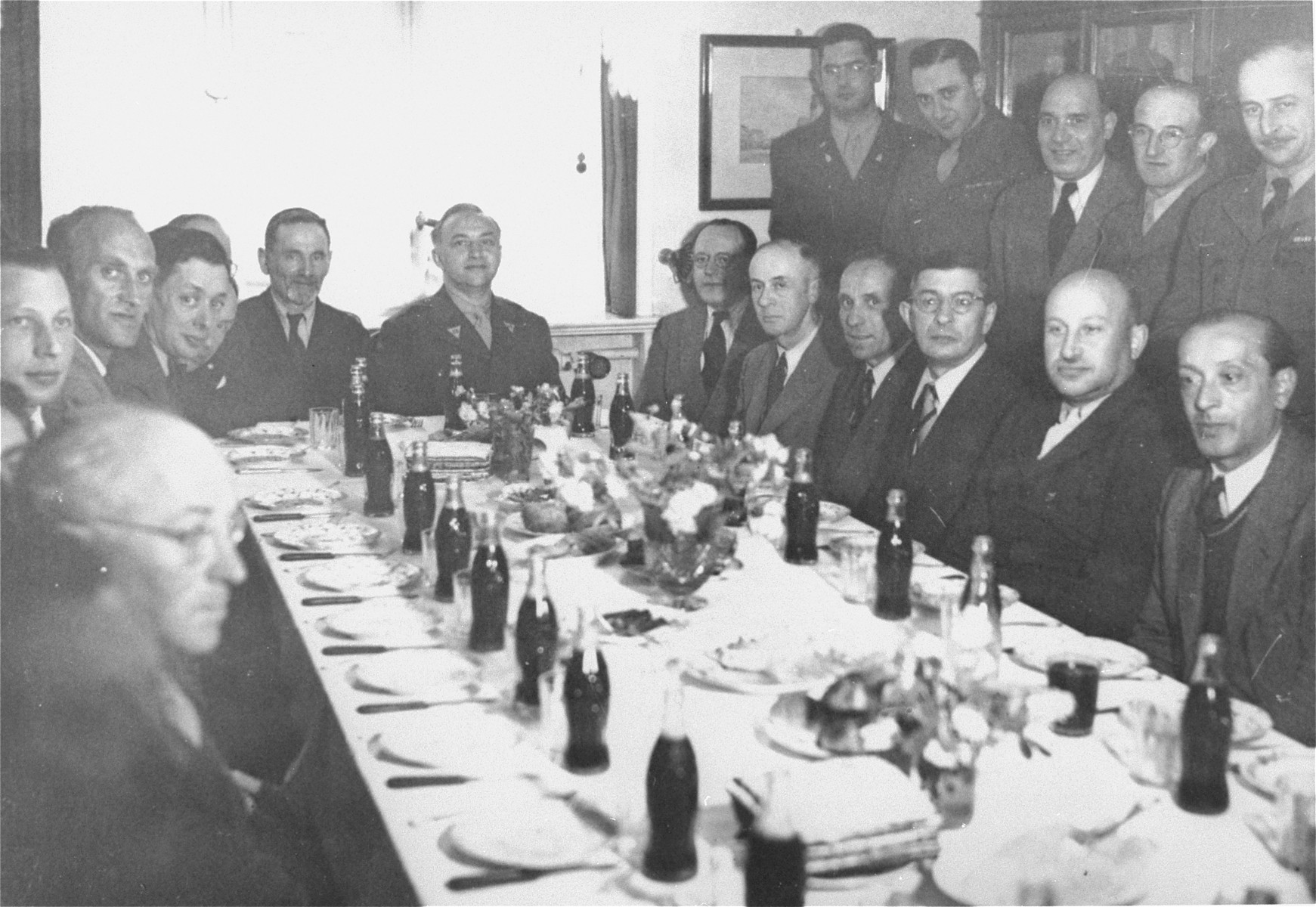 A dinner party in honor of General Joseph McNarney, the newly appointed commander of US forces in occupied Germany, at the Schlachtensee displaced persons camp in Berlin.  Among those pictured are Rabbi Philip Bernstein (at the head of the table in uniform); Chaplain Herbert Friedman (back row, first from the left); Eli Rock, JDC director for Berlin (next to Friedman); and Hans Erich Fabian (left side, leaning forward, near the head of the table).