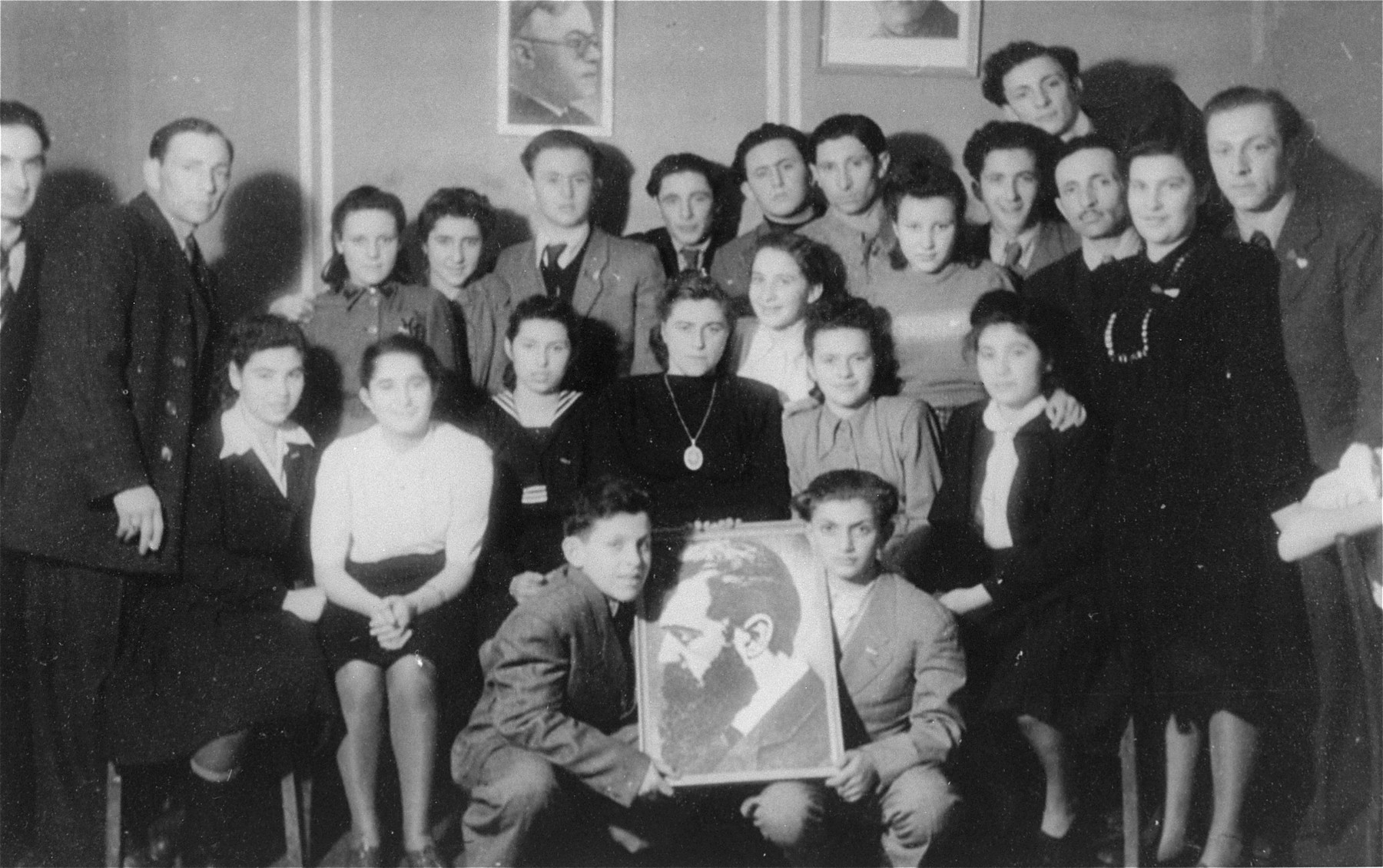 Members of Betar pose with a portrait of Theodor Herzl in the Schlachtensee displaced persons camp.    Pictured are the Zycer brothers, Icka Lewin, Mishka Gleiberman, Yurek Snyder, Leizer Snyder, and Murka Bimbad.