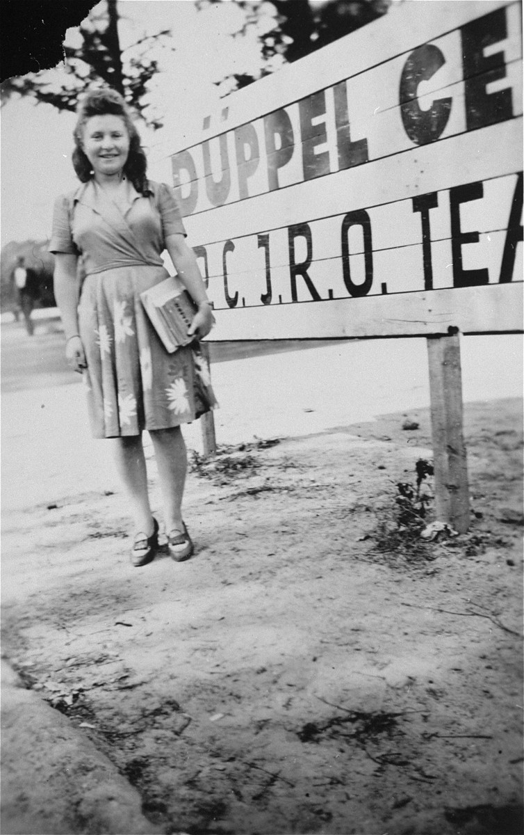 Lusia Gliklich stands in front of the entrance to Schlachtensee displaced persons camp.