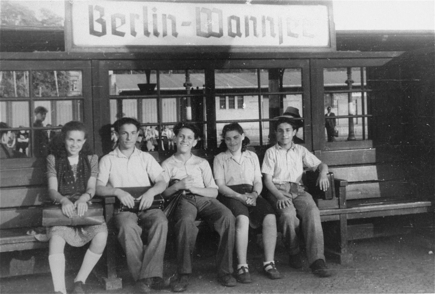 Five young DPs await a train at the Berlin-Wannsee train station.