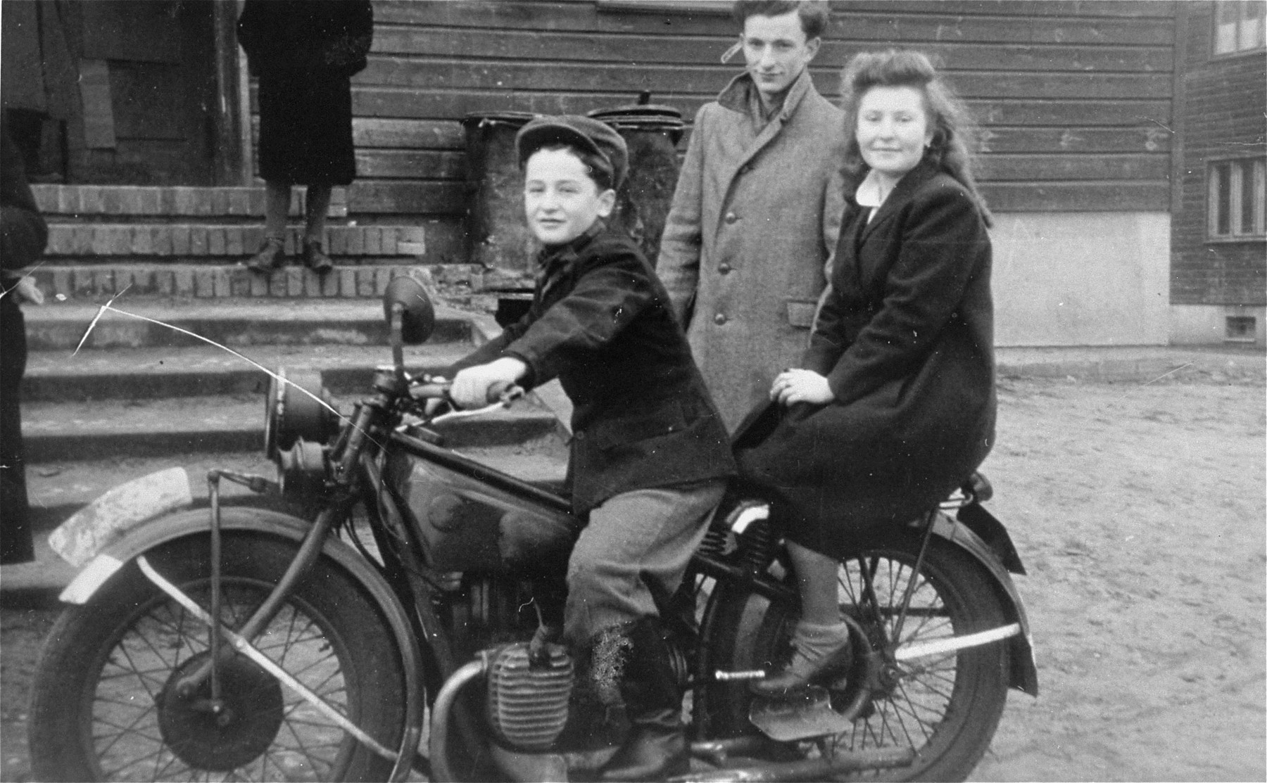 Moniek and Lusia Gliklich ride a motorcycle in the Schlachtensee displaced persons camp.    Yurek Snyder is standing behind them.