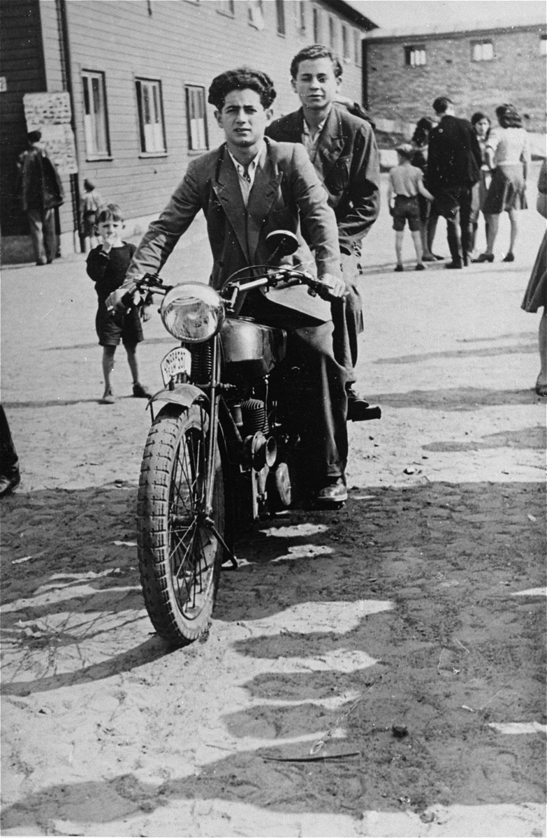 Young DPs ride a motorcycle along a thoroughfare in Schlachtensee displaced persons camp.