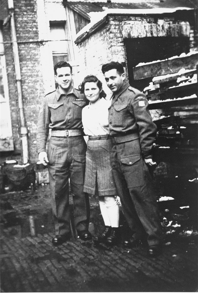 Jewish Brigade soldiers pose with a member of the Kibbutz Buchenwald hachshara who is waiting in Antwerp for passage to Palestine.