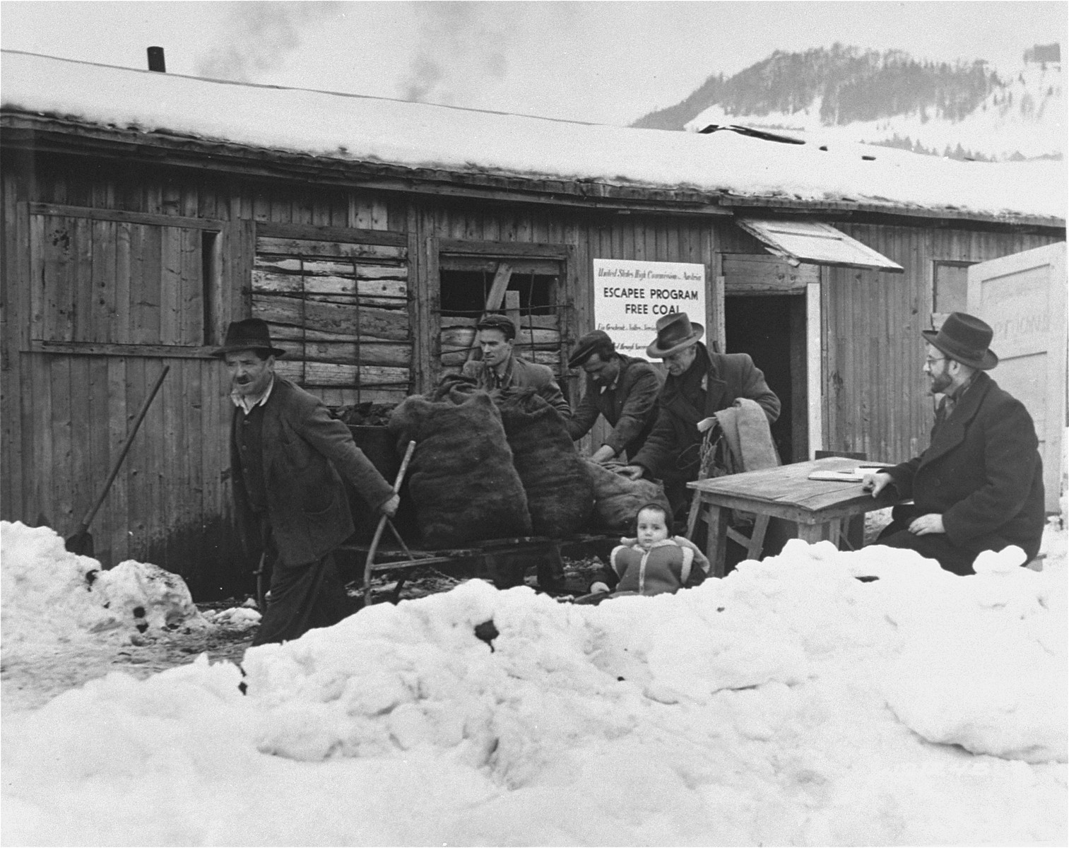 Coal is delivered to the Hallein displaced persons camp near Salzburg.  The shipment of coal was provided by President Truman's Escape Program.  Moses Kestenbaum, distribution supervisor, oversees the delivery.