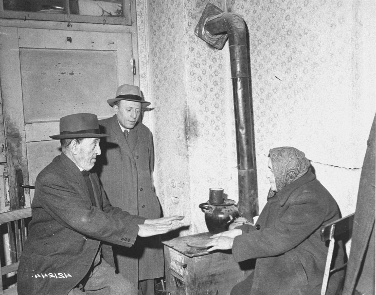 A Jewish DP family huddles around the stove which is used for heating and cooking at the Jewish DP camp located at Hallein, 15 miles from Salzburg.