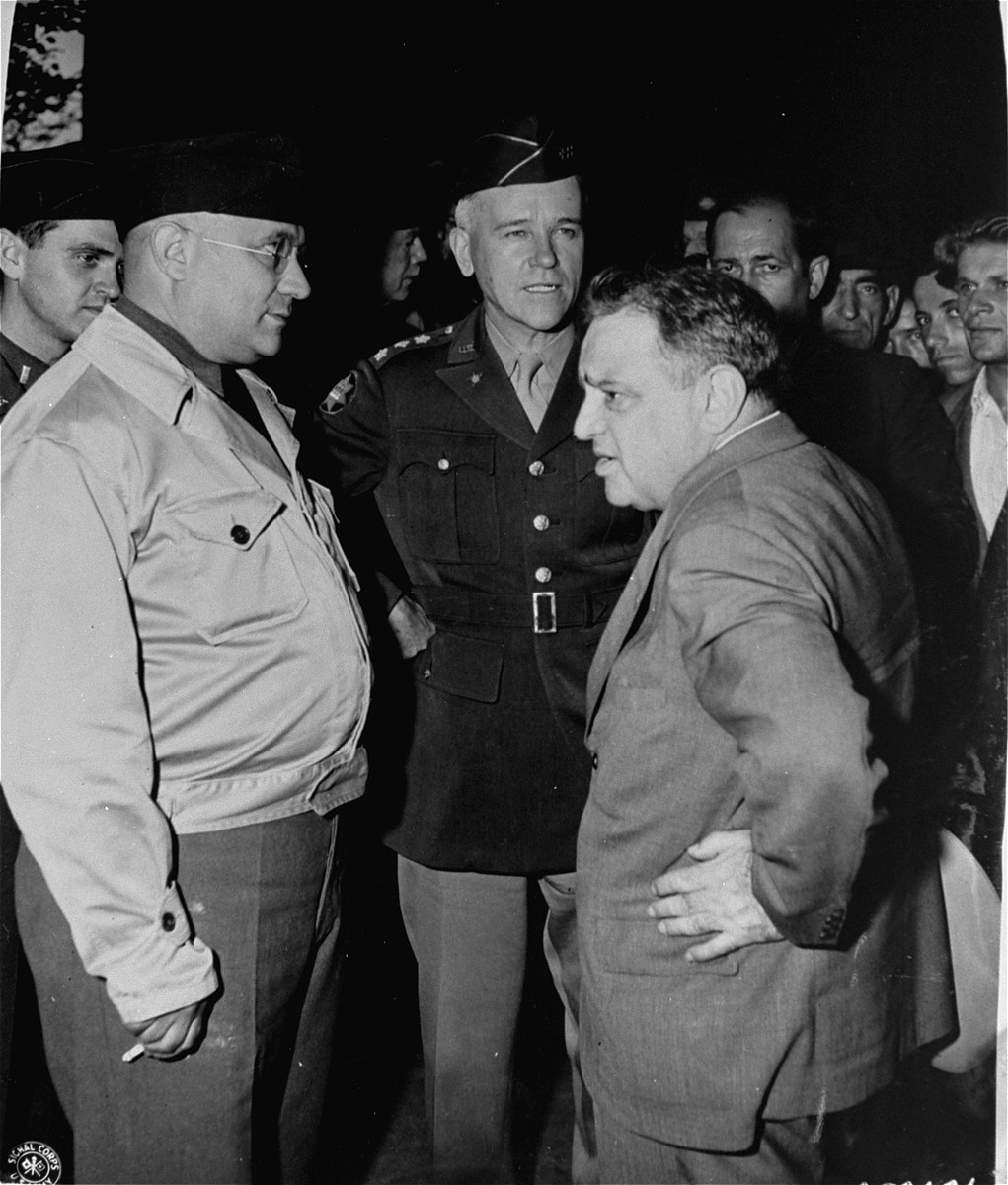 UNRRA Director General Fiorello LaGuardia speaks to General J. Lawton Collins (center) and UNRRA Schlachtensee camp director Harold Fishbein (left) during an official tour of the Schlachtensee displaced persons camp.  Also pictured in partially obscured on the left is Rabbi Mayer Abramowitz.